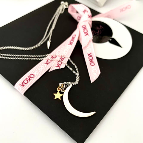 Leoni & Vonk silver moon and gold star necklace photographed on a black envelope