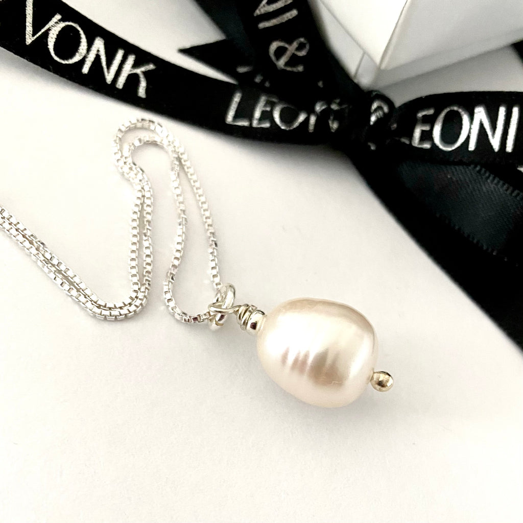 Leoni & Vonk white baroque pearl on a sterling sivler chain photographed near Leoni & Vonk ribbon.