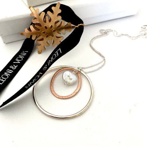 Leoni & Vonk stering silver and brushed rose gold plate and keshi pearl necklace near a christmas decoration and Leoni & vonk ribbon