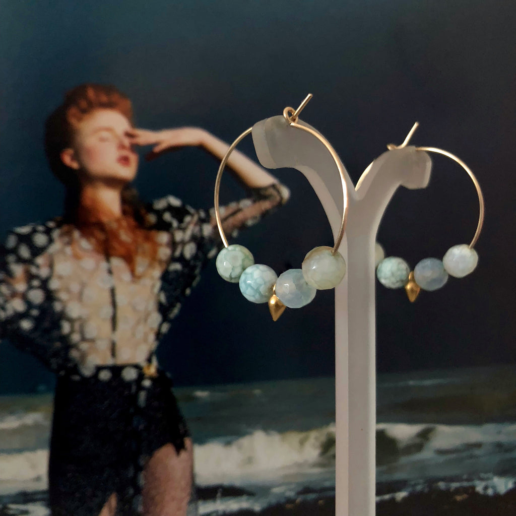 Leoni & Vonk gold fill hoop and aqua agate earrings photographed against a magazine page