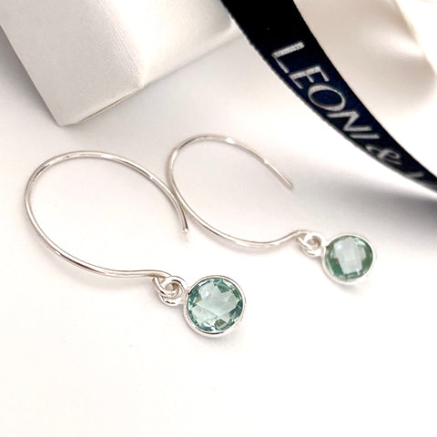 Leoni & Vonk aquamarine sterling silver dot hoop earrings photographed near a white box and Leoni & Vonk ribbon