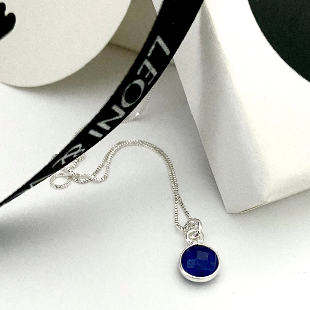 Leoni & Vonk sapphire and sterling silver necklace on a sterling silver chain photographed near a white box and leoni & Vonk ribbon