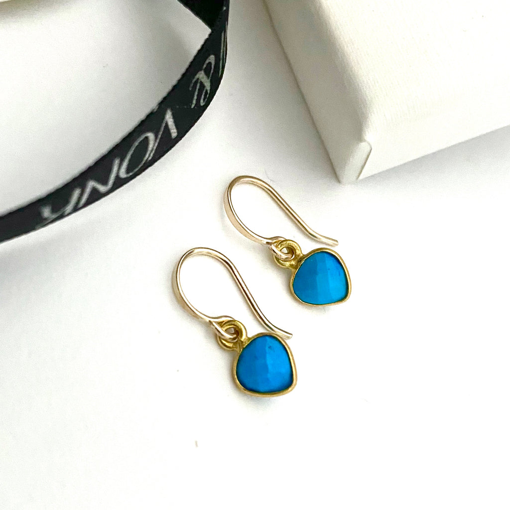 Leoni & Vonk turquoise heart december birthstone earrings photographed near a white box and Leoni & Vonk ribbon