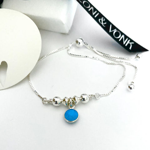 Leoni & Vonk sterling silver and turquoise December birthstone bracelet photographed near a white box and Leoni & Vonk ribbon