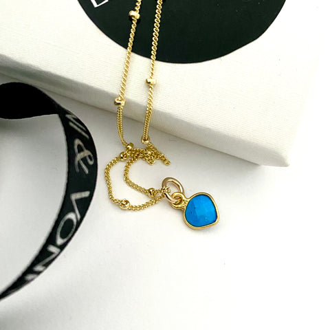 Leoni & Vonk turquoise heart on a gold fill bead chain photographed near a white box and Leoni & Vonk ribbon.