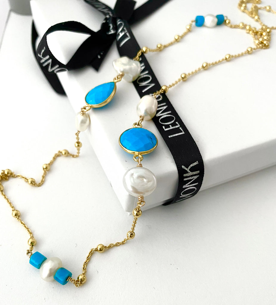 Leoni & Vonk turquoise, pearl adn gold necklace photographed on a Leoni & Vonk box
