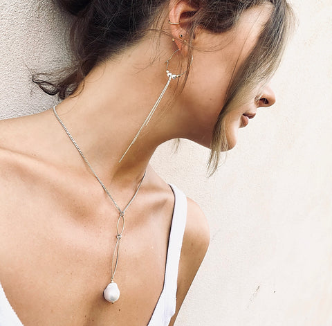 Model wearing Leoni & Vonk Melissa gold hoop and silver tassel earring and Robyn pearl necklace