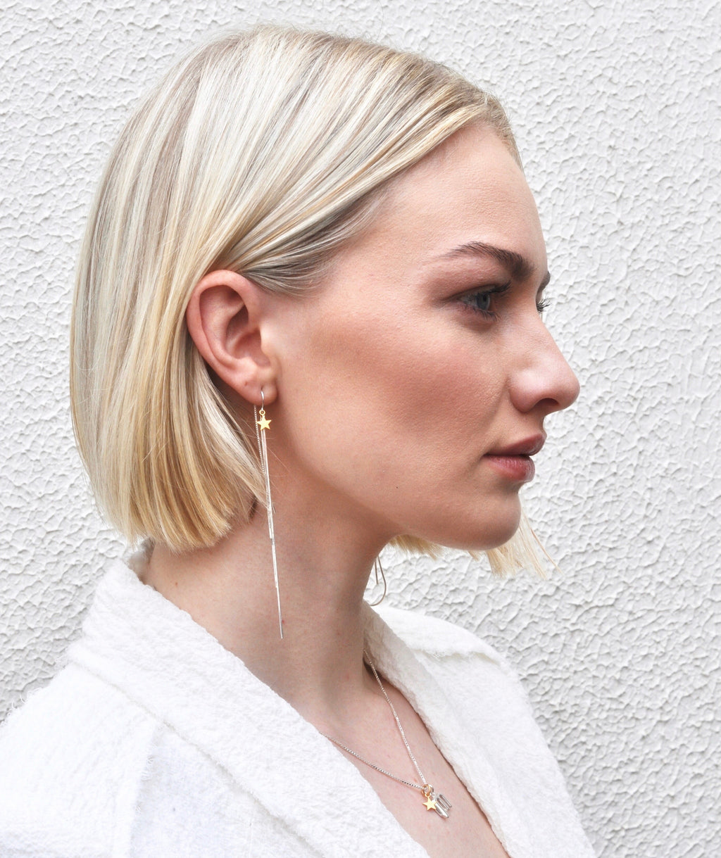 Model wearing Leoni & Vonk electra earrings and white jacket