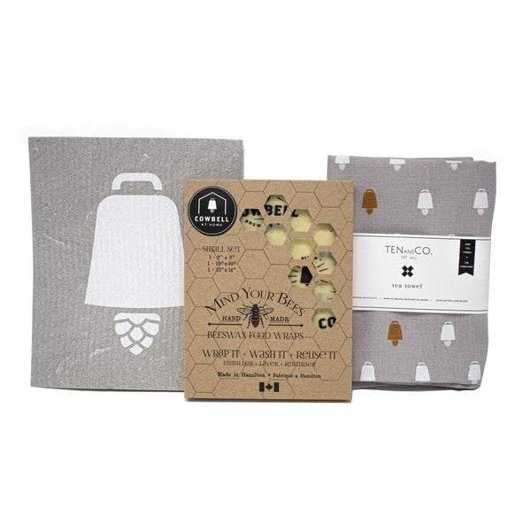 Mind Your Bees Beeswax Food Wraps (set of 3, with Cowbell logo), Ten and Co tea towels (one grey tea towel, with white and copper Cowbell icons), and one Ten and Co reusable dishcloth (grey with large white Cowbell icon).