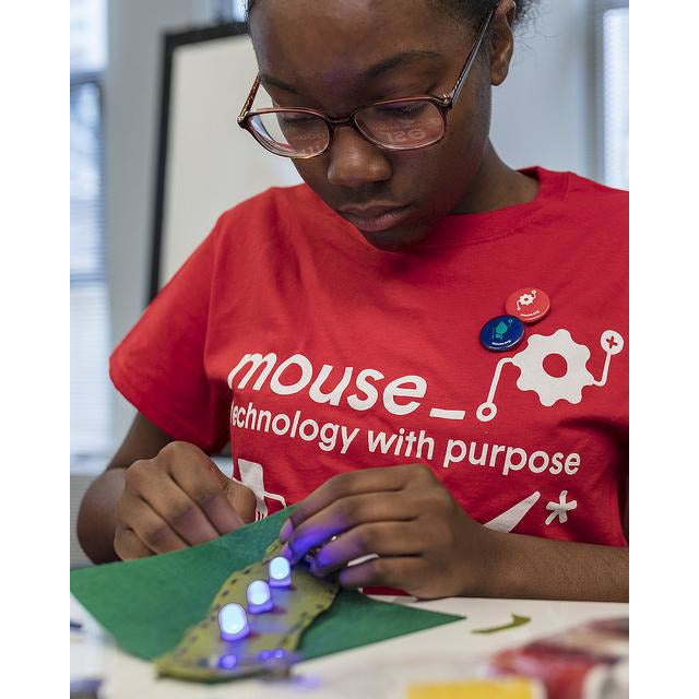 "Female student wearing red shirt reading ""mouse: technology with purpose"" crafting with electronics components"