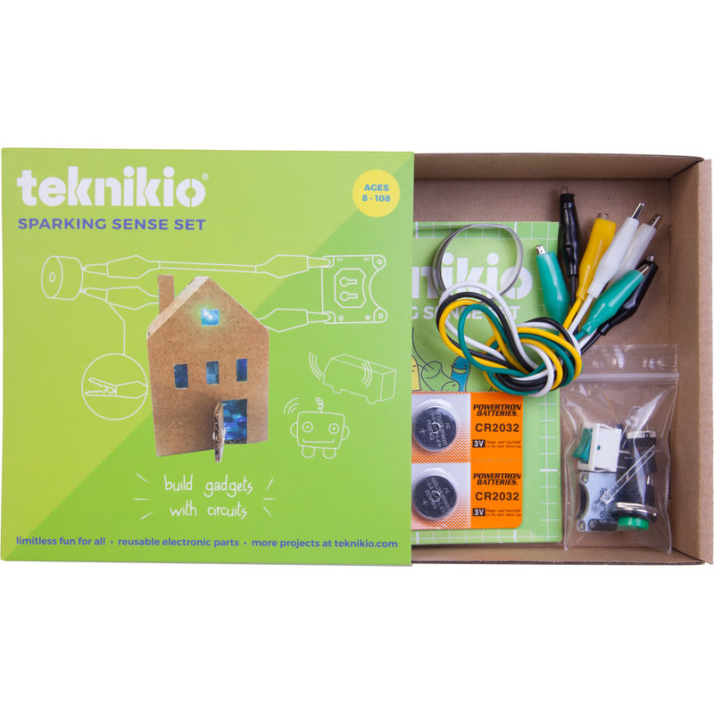 Teknikio Sparking Sense kit partially opened to reveal kit contents, including alligator clips, conductive tape, batteries, and electronic components