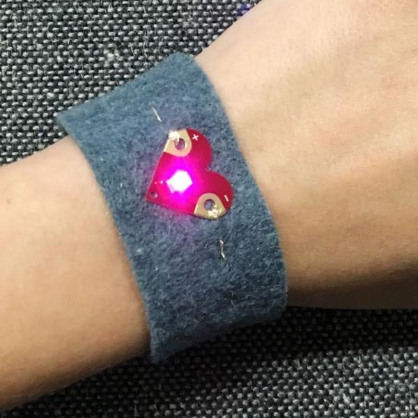 Photo of hand wearing grey wristband with Teknikio heart LED sewn on