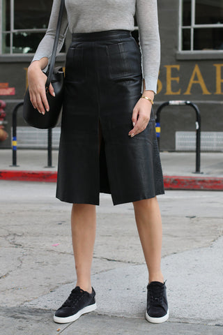 Cities Skirt from Aje is a leather midi skirt that has a high waist, belt detail and front slit.