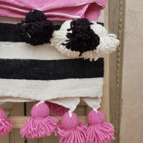 pink pompom blanket with black stripes