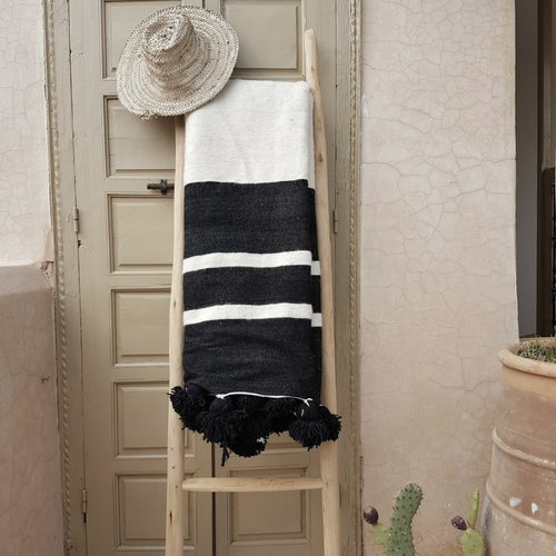 white pompom blanket with black stripes