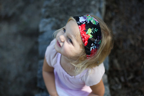 little girl wearing a black headband with pink and red flowers