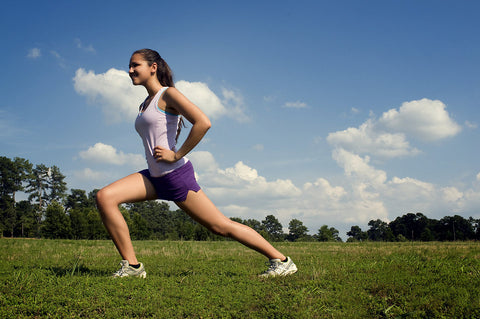 Woman stretching outside before cardiovascular exercise.
