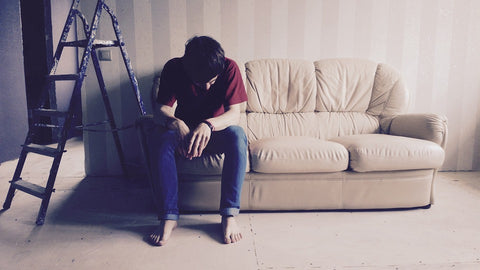 Man sitting on a couch in an empty room.