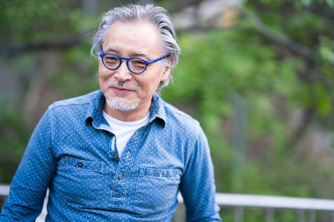 Man with blue shirt and glasses smiling.