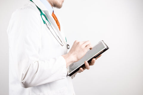 Man in white lab coat using tablet