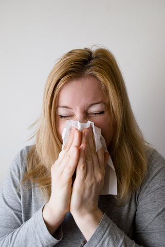 Sick woman blowing her nose in a Kleenex