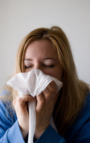 Woman blowing her nose into a Kleenex.