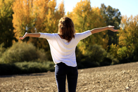 Woman standing on a hill with her arms stretched out