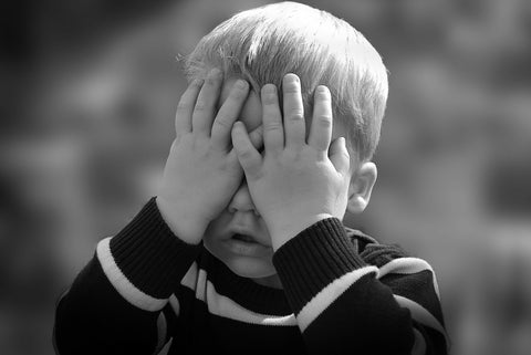 Black and white image of small child touching his face.