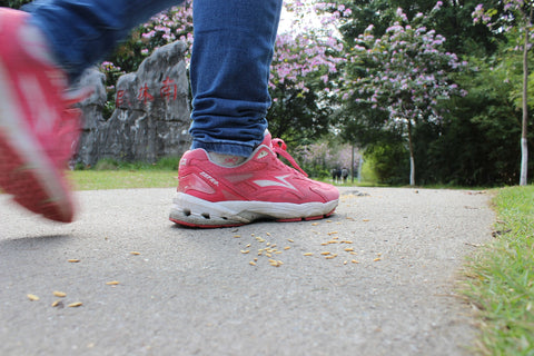 Woman with pink shoes walking through a park.