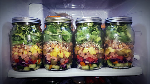 Fridge with mason jars containing fruits and vegetables