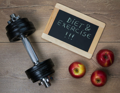 "Dumbbell, three apples, and a chalk board with the words ""diet & exercise"" written on it."