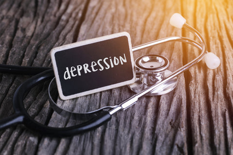 """Stethoscope and card lying on a table with the word """"depression"""" written on it."""