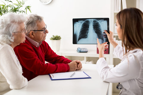Doctor explaining chest x-ray to elderly patients.