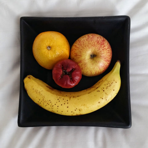 Fruit on a plate arranged in the shape of a smiley face
