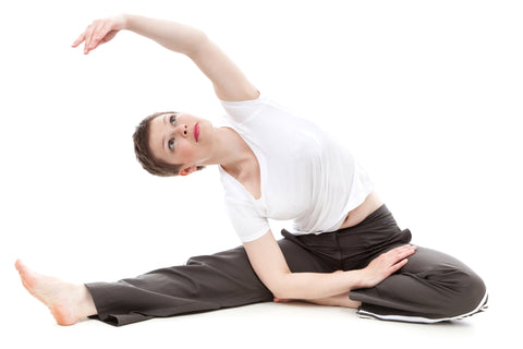 Woman in white shirt and sweat pants stretching while sitting on the ground.
