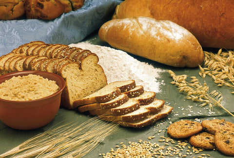 Bread, wheat, grains, and cookies displayed on a green tablecloth