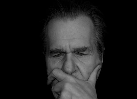 Black and white image of elderly man touching his face.