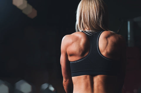 Woman with back flexed lifting weights.
