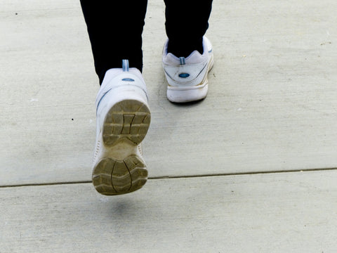 Woman with white shoes walking down the sidewalk.