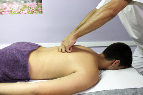 Man lying face down getting a professional massage.