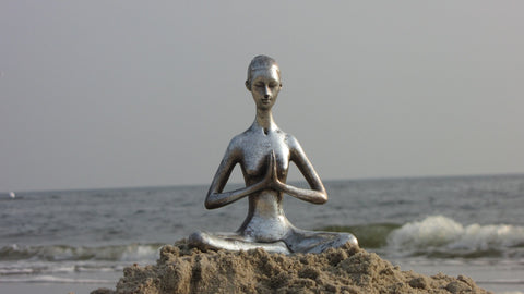Statue of someone meditating on a mound of sand on a beach