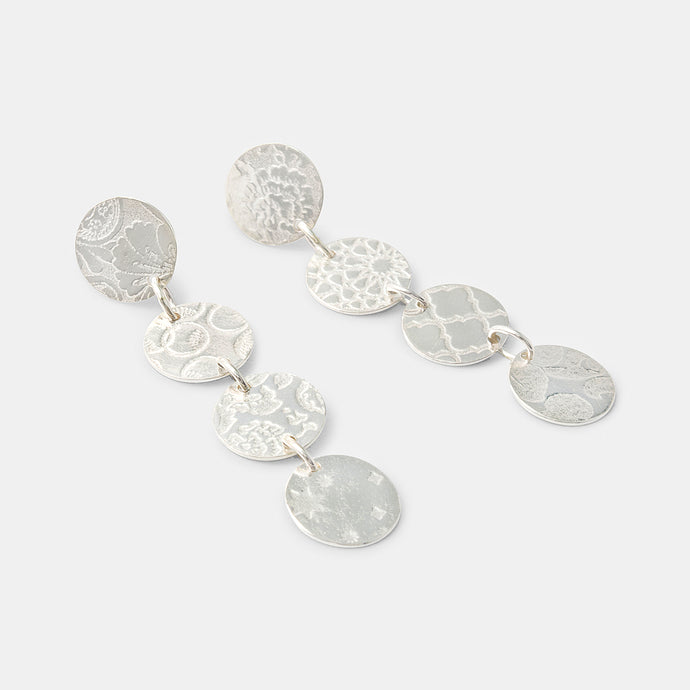 Handmade silver dangle earrings with dotted patterns. By handmade jewelry designer Simone Walsh.