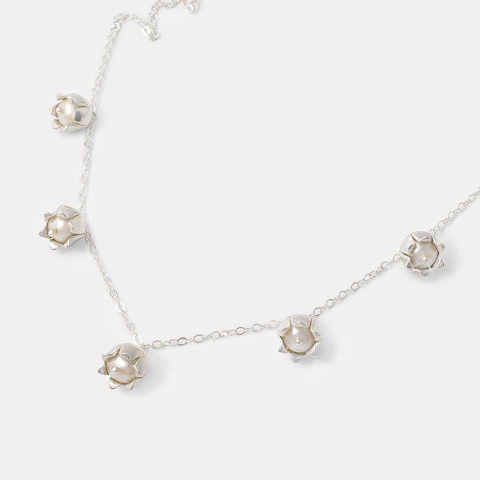 Beautiful pearl and sterling silver chain necklace for women with lily of the valley flowers by handmade jewelry designer Simone Walsh.