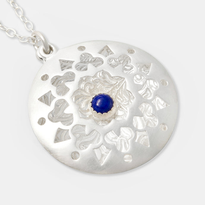 Handmade statement jewelry: sterling silver open locket pendant with a mandala design and lapis lazuli gemstone. Created by handcrafted jewelry designer Simone Walsh.