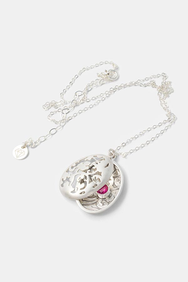 Beautiful handmade silver jewelry: unique statement necklace in an open locket necklace design. Victorian inspired leaves pattern with a ruby gemstone. Beautiful jewelry in sterling silver in our handmade jewelry store.