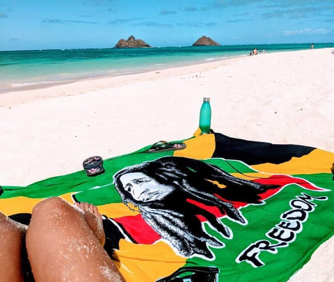 Bob Marely Freedom Sarong or Pareo laid out on the beach with someone laying on it