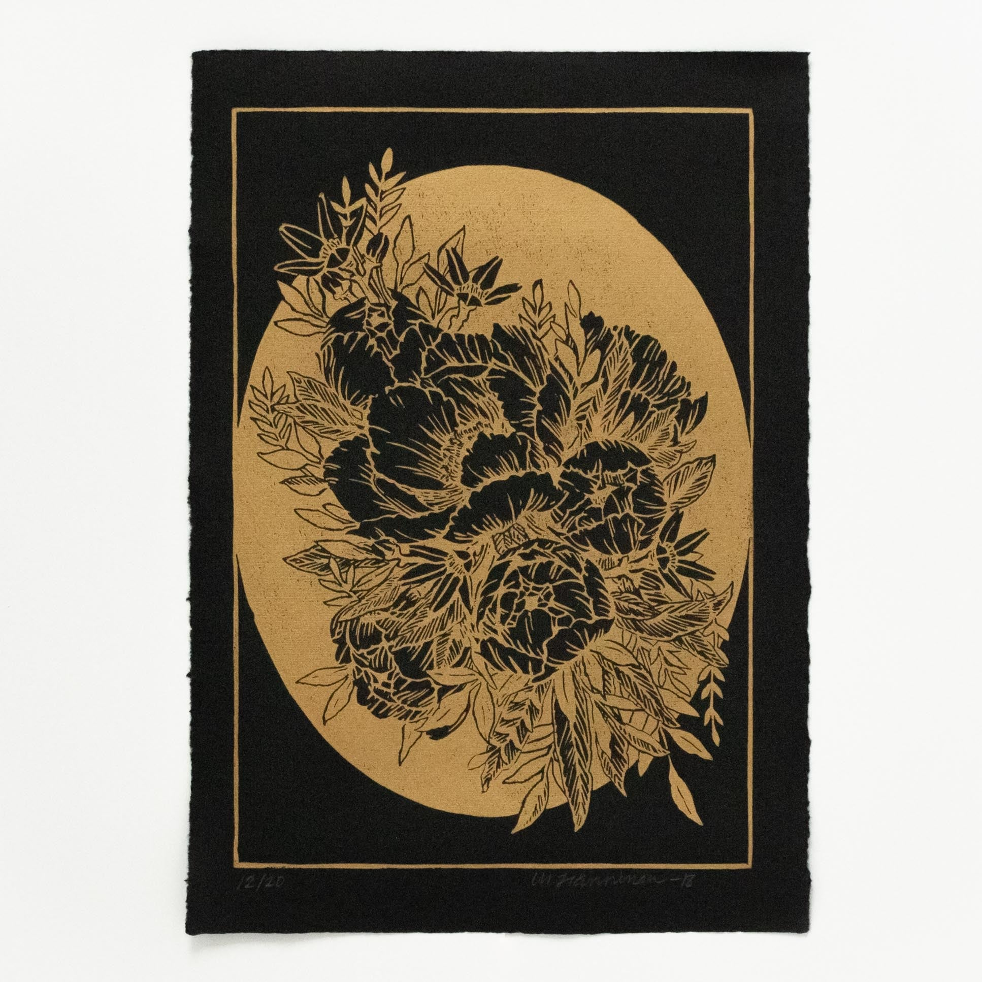 A floral linocut print of bucket of peonies and oval shaped background, printed with gold ink on black A4 paper.