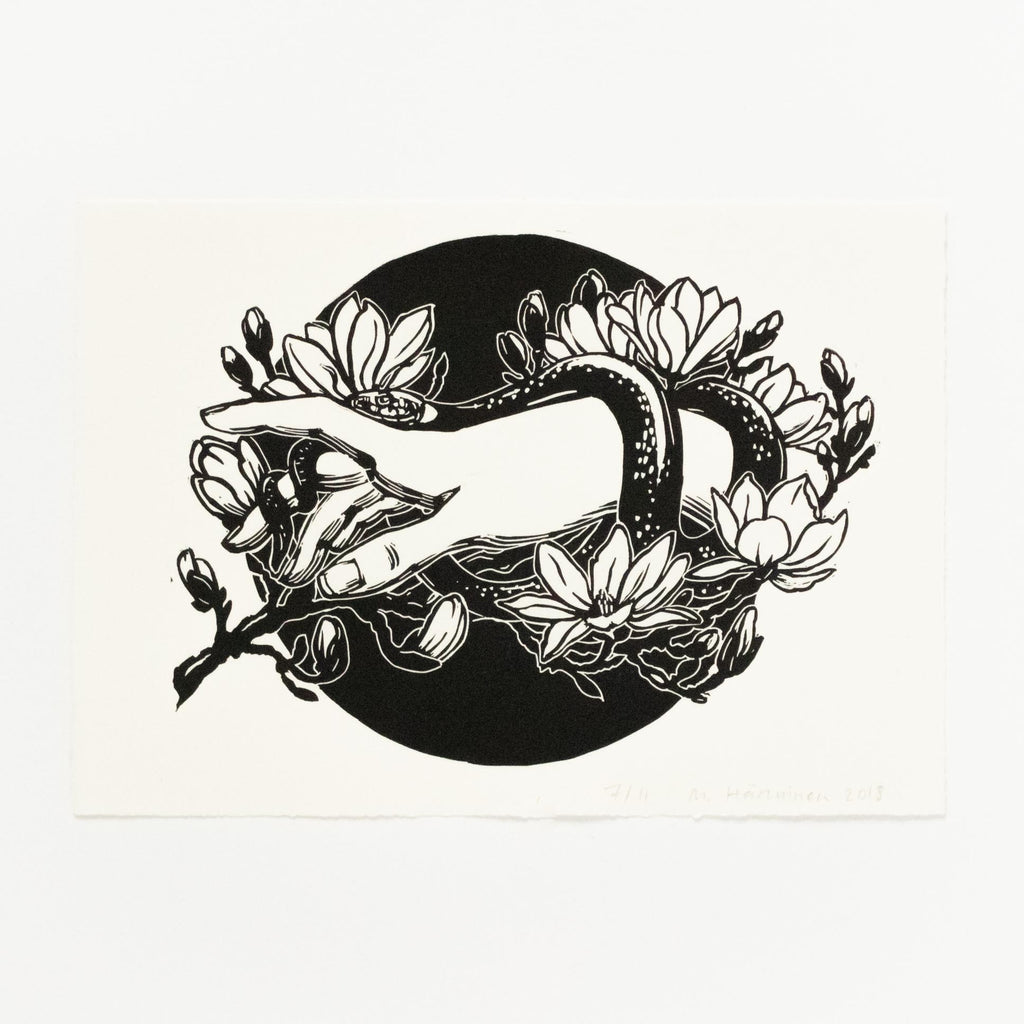Black and white linocut art print of a hand and a grass snake, white magnolia flowers, and circular background.