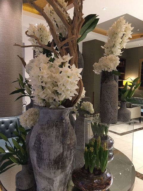 White tall corporate flowers installation in hotel lobby.