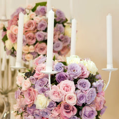 Pink wedding flower arrangement with candles.